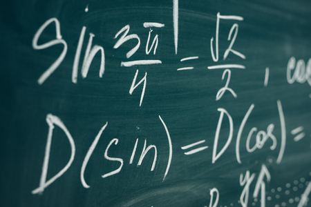 Trigonometric equation written on the chalkboard. School curriculum. Фото со стока