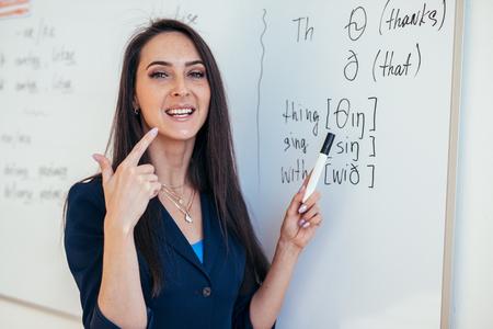 El profesor de la lección de inglés muestra cómo pronunciar los sonidos Foto de archivo