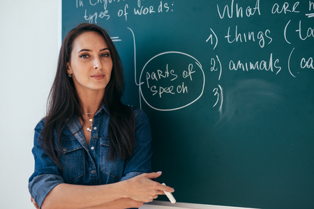 Chica estudiante de pie junto a la pizarra en el aula