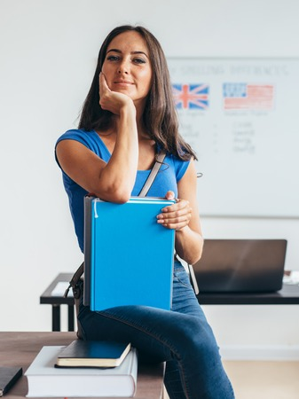 Female student sitting at table smiling and looking at camera.