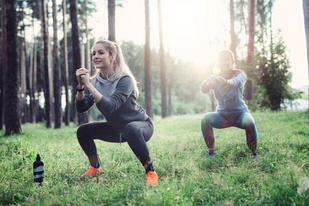 Fit young Caucasian women wearing jumpsuits working out in the forest doing squats in the early morning Stock Photo