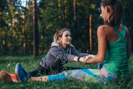 Two girls doing partner stretching yoga exercise, Paschimottanasana or seated forward bend pose, working-out outdoors