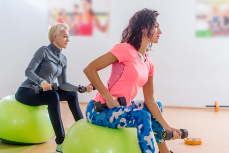 Sporty slim women taking part in gym fitness class exercising sitting on physioballs doing alternated biceps curl with dumbbells Stock Photo