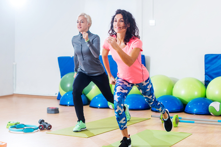 Two athletic female friends working out in a gym doing reverse lunge knee-up exercise Stockfoto