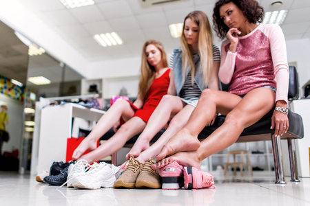 Close-up view of barefoot long slim female legs surrounded by variety of sports shoes. Three female friends sitting resting after shopping in a shopping mall