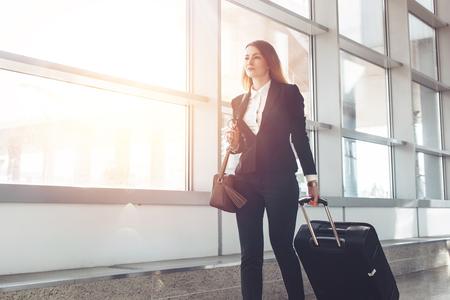 Assistente di volo femminile abbastanza sorridente che trasporta i bagagli che vanno all'aereo nell'aeroporto