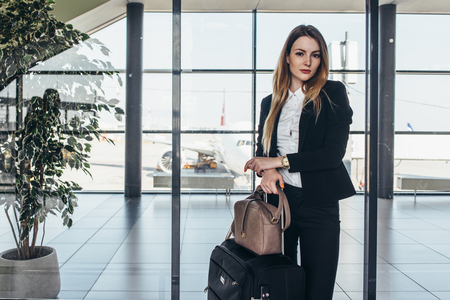 Beautiful airhostess standing in her uniform with her bags ready for a flight