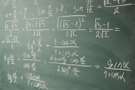 Algebra, mathematics. Trigonometry and elementary functions written on the chalkboard.