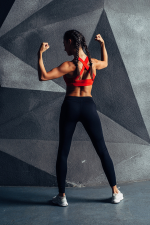 Back view portrait of a fitness woman showing biceps Stock Photo