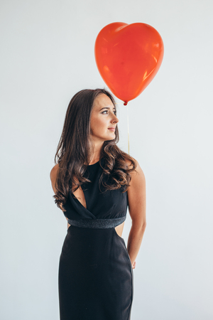 Cute brunette woman standing smiling and playing with balloons.