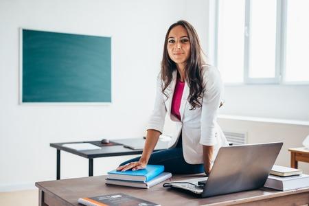 Porträt der weiblichen Hochschullehrerin, die in die Kamera lächelt