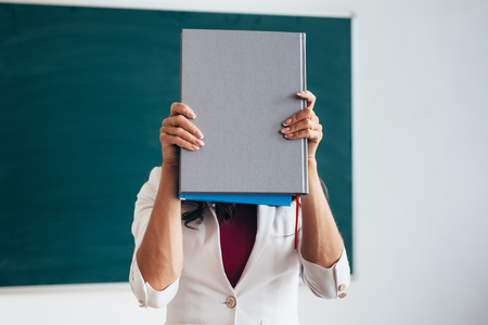 Female student standing near blackboard with book