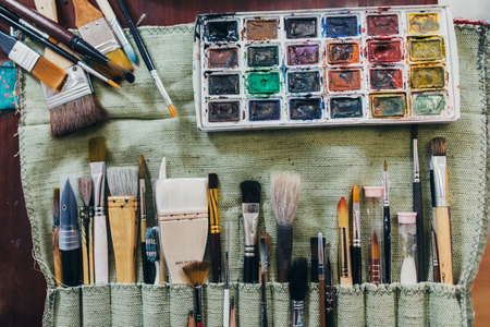 Art supplies. Brushes different types for drawing, watercolor paints.