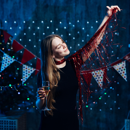 Girl playing with red tinsel Christmas New Year. Stock Photo