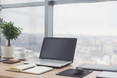 Workplace with notebook laptop Comfortable work table in office windows and city view. Imagens