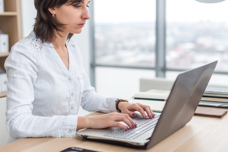 Office worker typing, working at her workplace, using laptop.