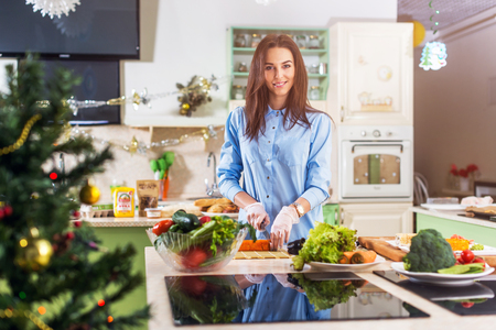 Young Caucasian lady cooking New Year or Christmas meal in decorated kitchen at home