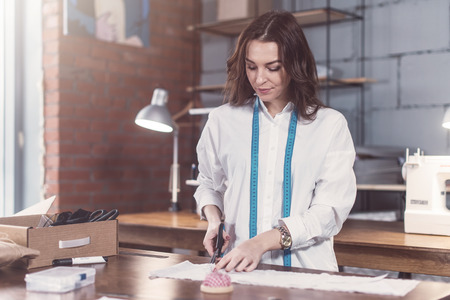 Pretty young fashion designer cutting cloth using scissors while working in studio Stock Photo