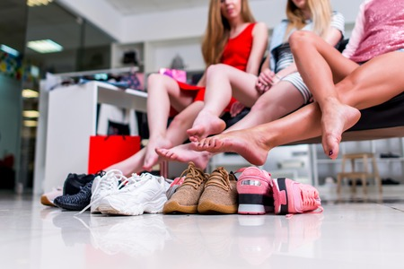 Young smiling girlfriends sitting in a clothing store looking at their bare feet and pile of new shoes and laughing