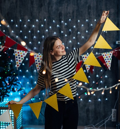 A young woman decorates room Flags, garlands preparing for the celebration Christmas.