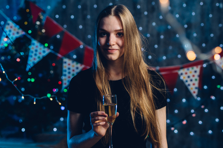 Young woman with glass of champagne. New Year, Christmas
