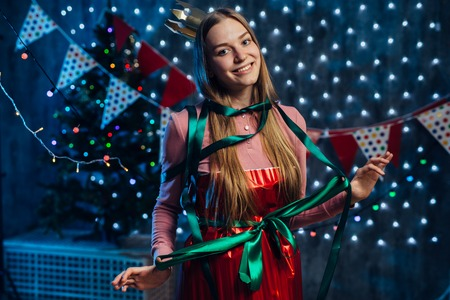 Girl wrapped in paper with a ribbon bow at body as a gift Imagens