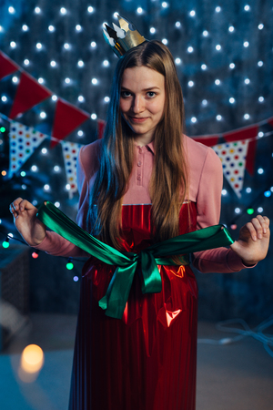 Portrait of young woman with big ribbon bow at body
