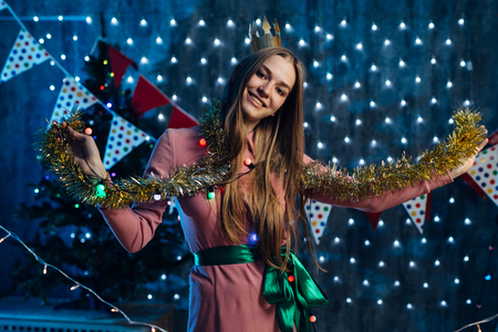 Girl playing with tinsel Christmas New Year.