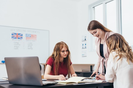 Young woman teaching English to adult students at language school. Stock Photo - 111081502