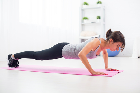 fit woman doing push-ups on the floor in her living room an exercise mat at home Stock Photo