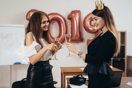 Young business women celebrating Christmas, New Year in office