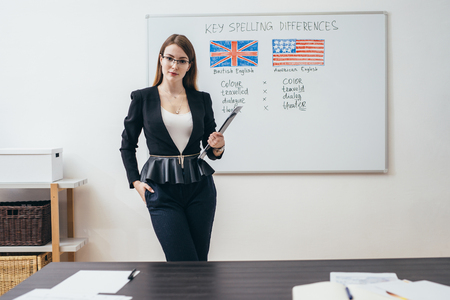 Female teacher with books in classroom English language school.
