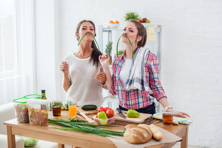 Women preparing healthy food playing with vegetables in kitchen having fun concept dieting nutrition Reklamní fotografie - 113204537