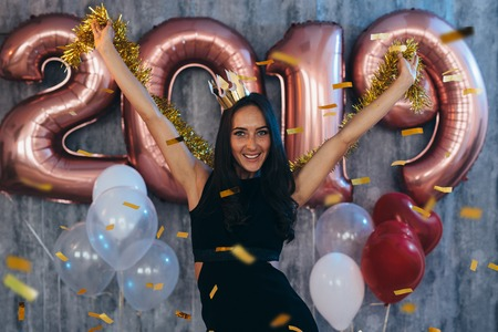 Woman in black dress and yellow crown celebrating new year, having fun Foto de archivo