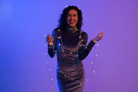 Portrait of young woman with hanging christmas lights on her body