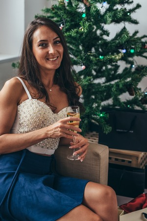 Woman siting by the christmas tree and taking a present out of shopping bag