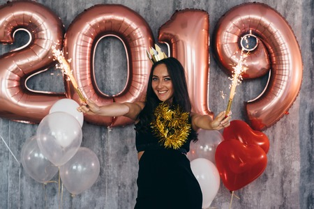 Woman holding balloons looking at camera. Celebration holiday new year Banque d'images - 113206595