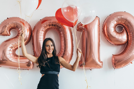 Woman holding balloons looking at camera. Celebration holiday new year Banque d'images - 113206596