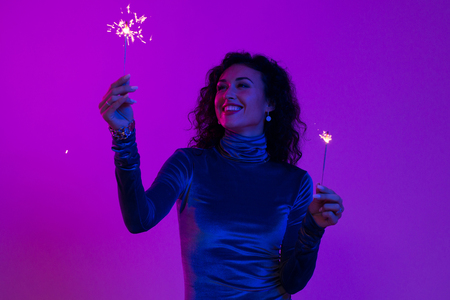 Woman holding festive burning sparkler and having fun. New year, Birthday, Holiday, Event, celebration, fun.