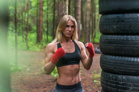 Woman boxer professional fighter posing in boxing stance, working out outdoors Stok Fotoğraf