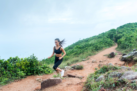 Sporty young woman in black sportswear trail running on mountain nature path. Fit girl jogging downhill rocky track. Stock Photo - 115312142