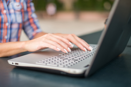 Close up shot of female hands typing on a laptop keyboard
