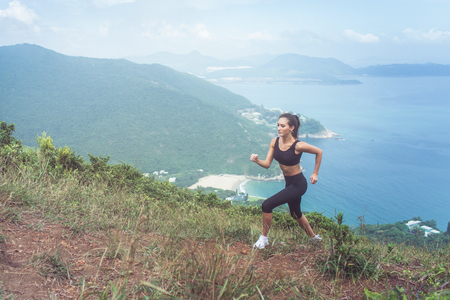 Slender young female athlete doing cardio exercise going up the mountain with sea in background. 写真素材