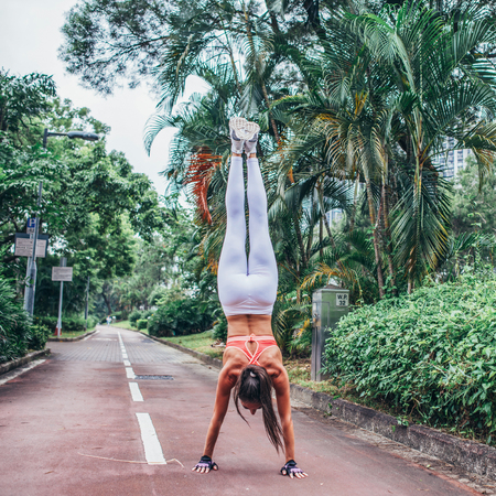 Rear view of fitness woman doing handstand exercise standing str Stock Photo