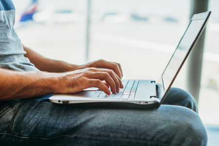 Young man using laptop in airport terminal Stock Photo - 115313486