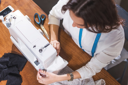 Top view of needlewoman stitching fabric on sewing machine at workplace in studio Stockfoto
