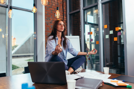 Portrait of attractive businesswoman practicing yoga sitting on desk at her workplace