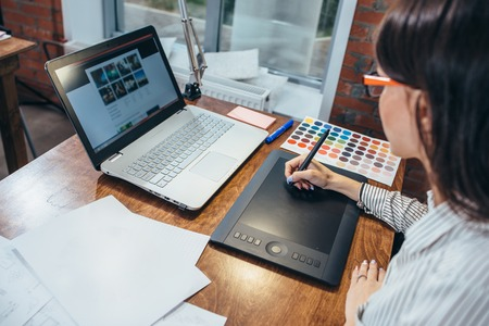 Close-up image of women drawing a project using a graphic tablet and a laptop sitting in modern office Foto de archivo