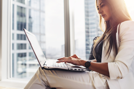 Young woman working on laptop sitting at home Standard-Bild