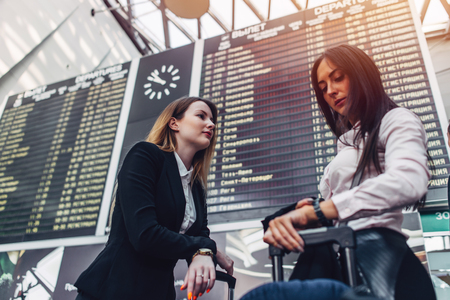 Two female tourists standing near flight information display in international airport